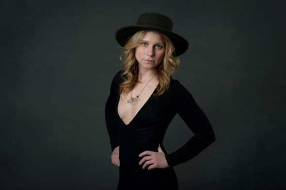 blonde model wearing a v-neck black dress, crystal necklace and wide brimmed hat for a headshot in South Jersey