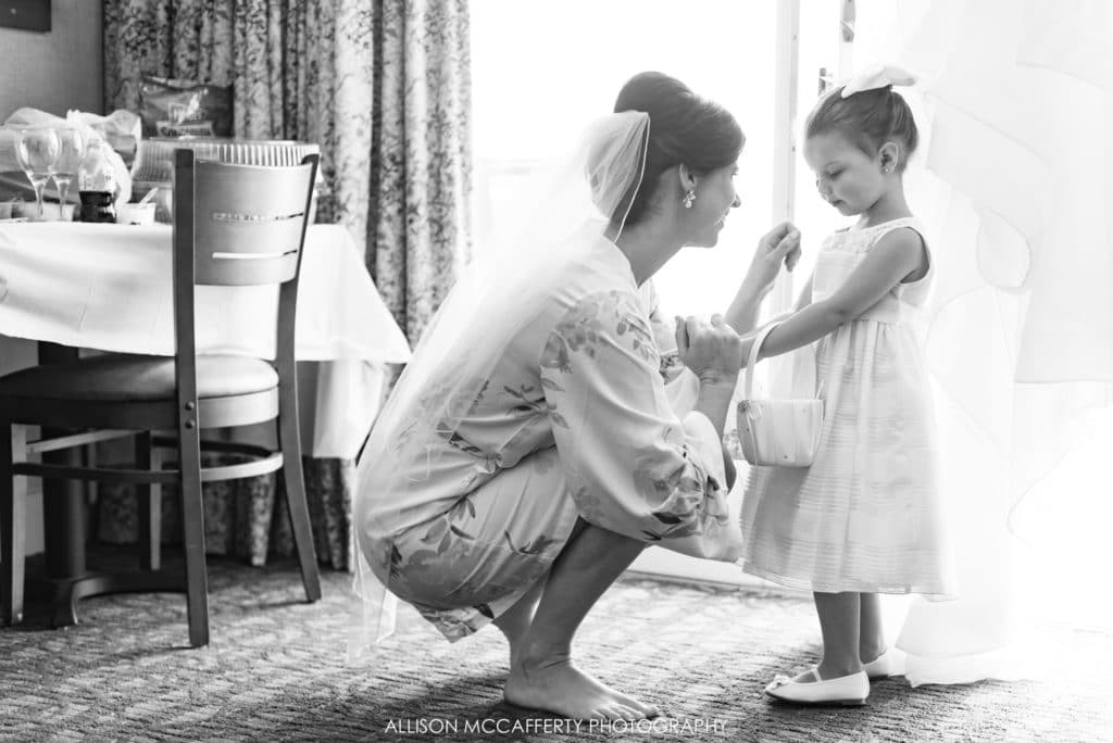 Bride talking with flower girl in robe