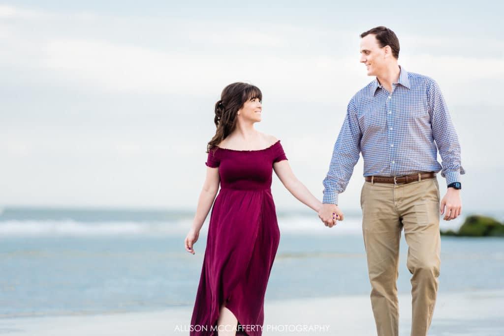 couple holding hands on the beach walking