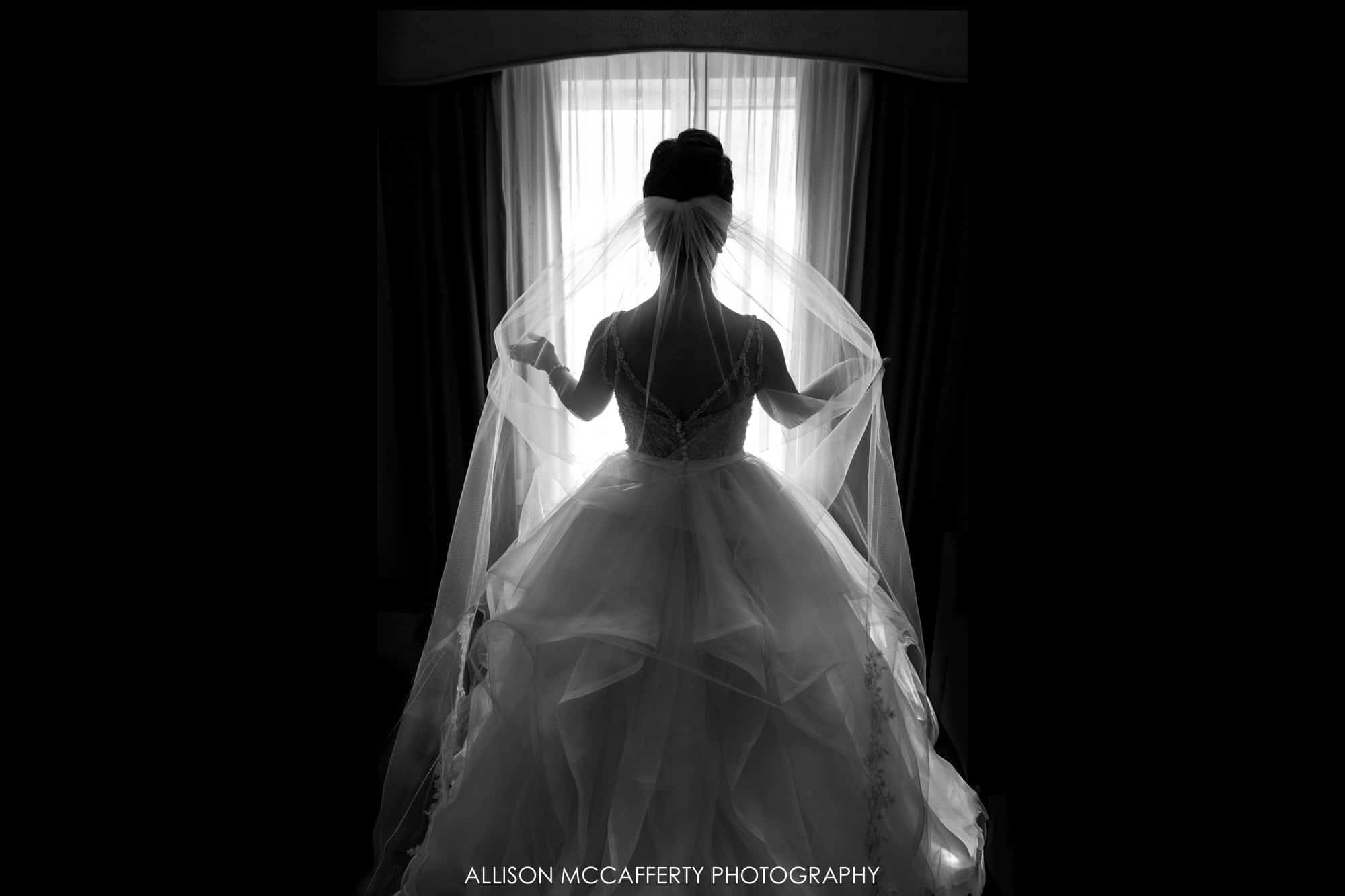 Black and White silhouette of a bride with her veil
