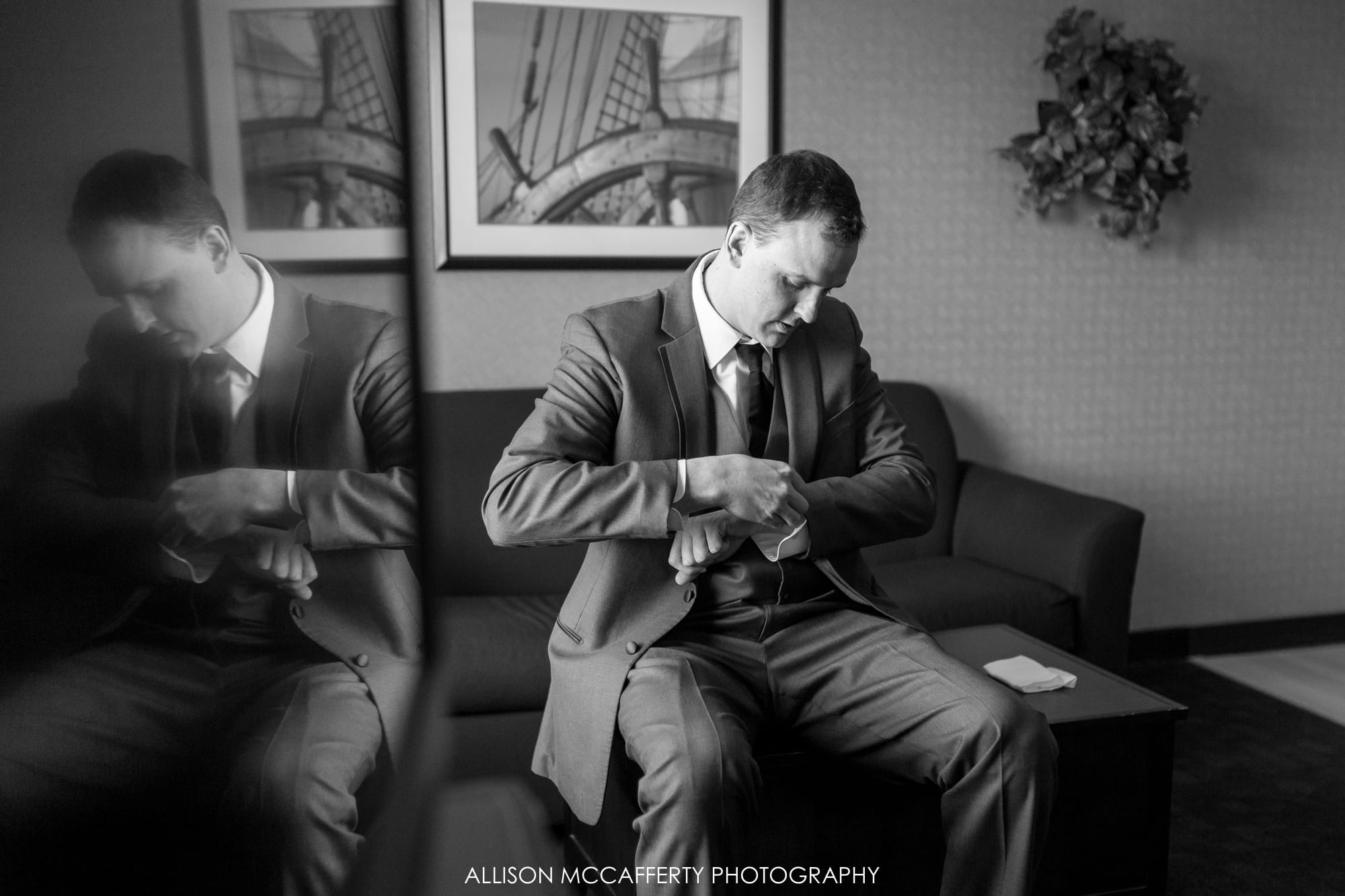 Groom getting ready in hotel room with a reflection