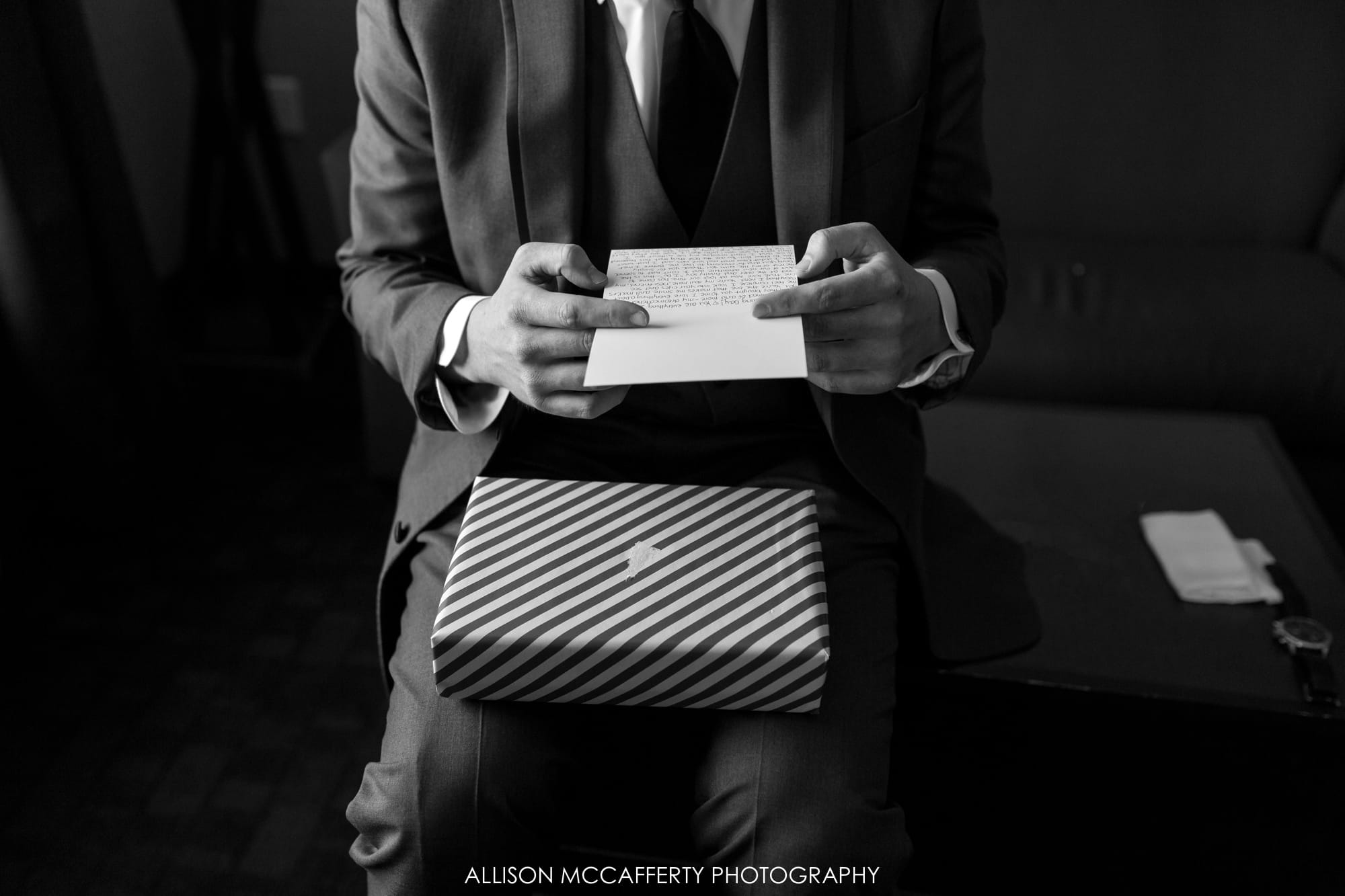 Groom opening a gift from his bride