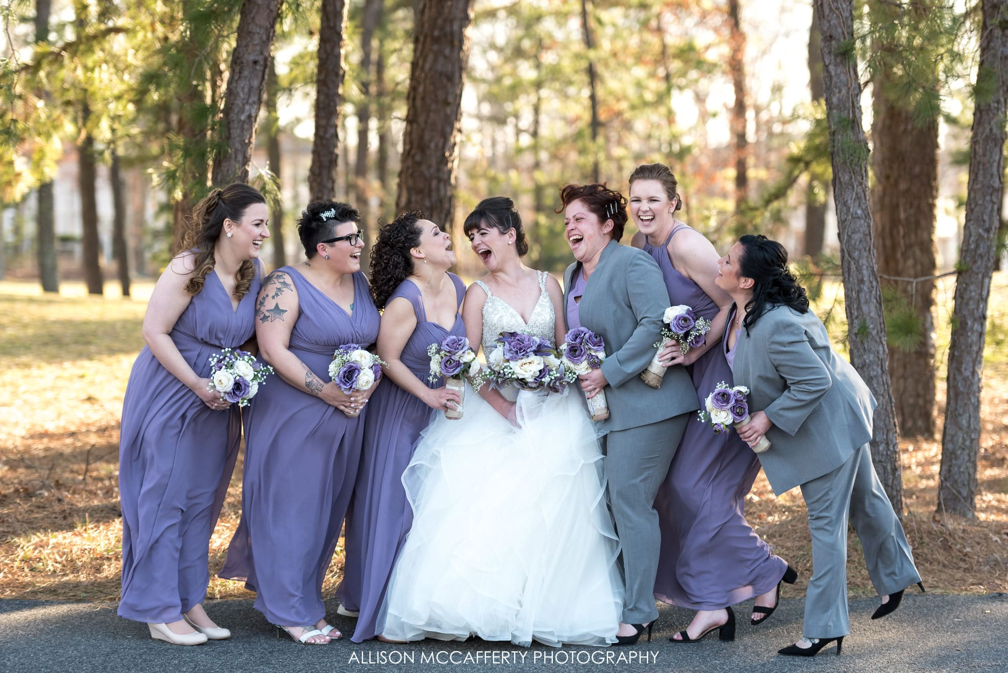 Bridemaids in purple dresses laughing with the bride