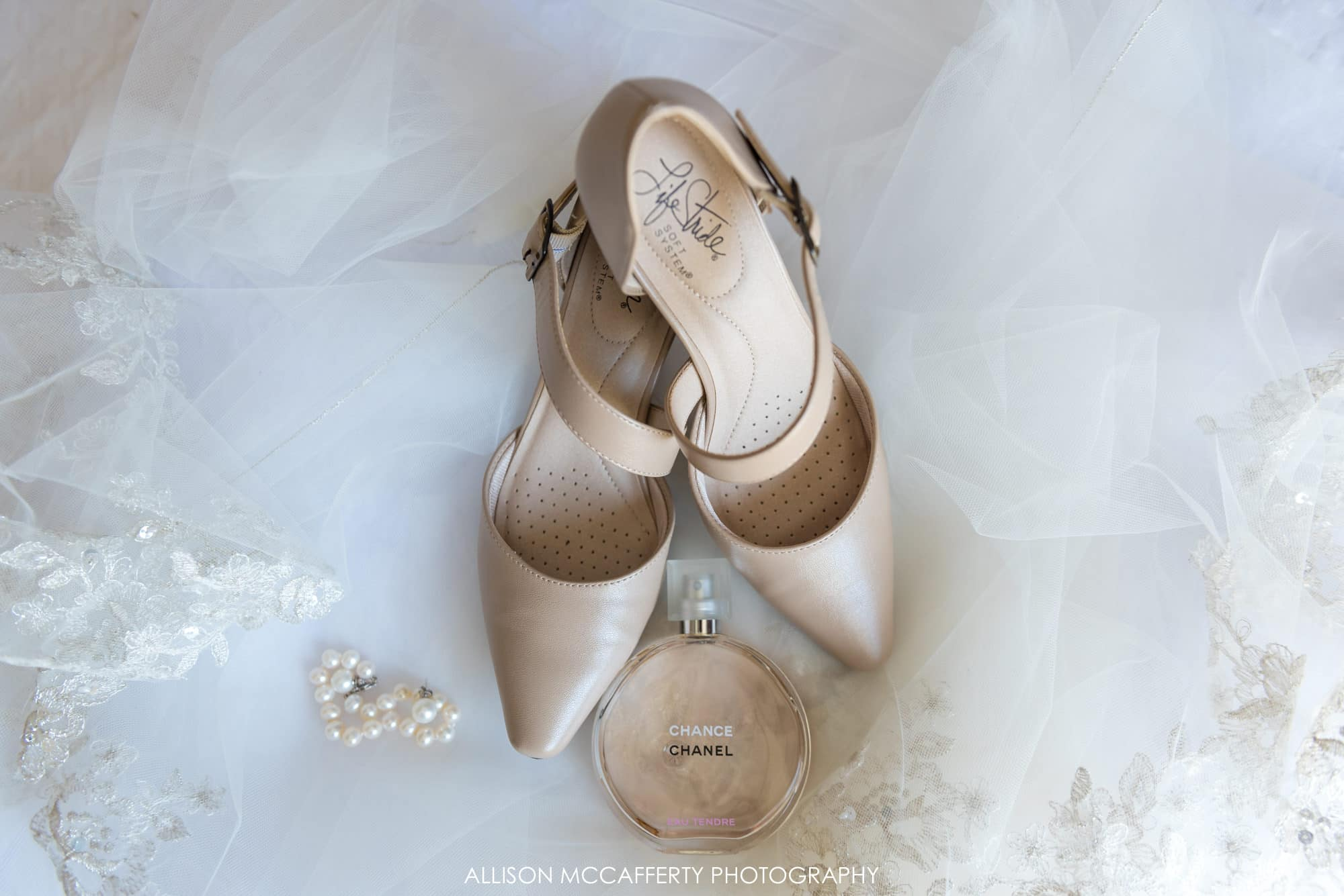 Wedding details, shoes, jewelry and perfume on a lace veil