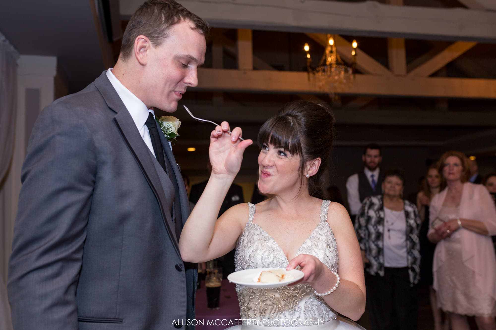 Bride feeding her husband cake during their wedding Blue Heron Pines Wedding Photos