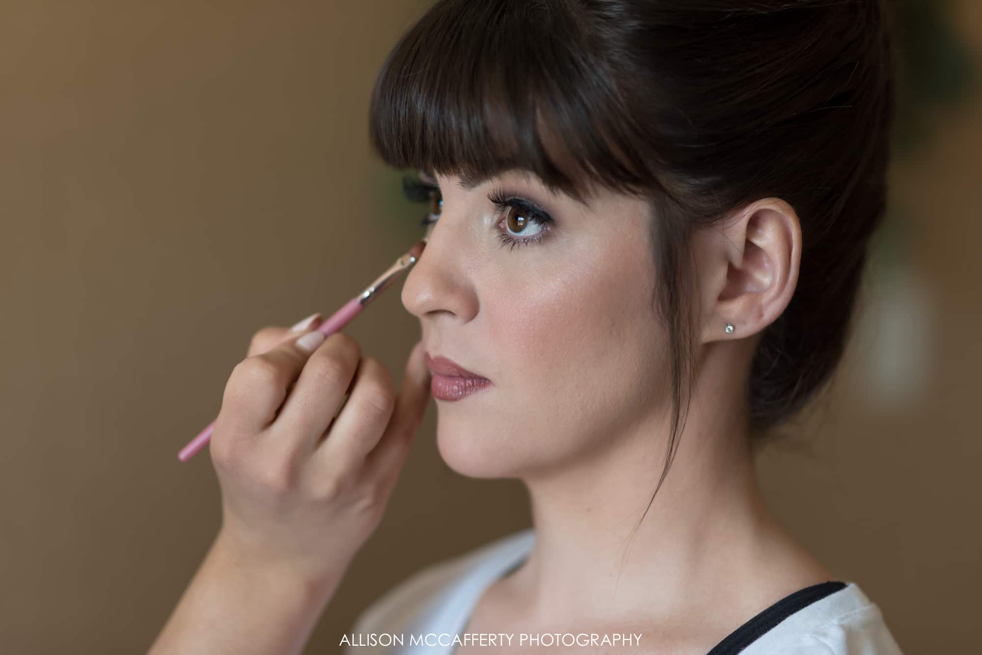 Brunette bride with bangs getting makeup done