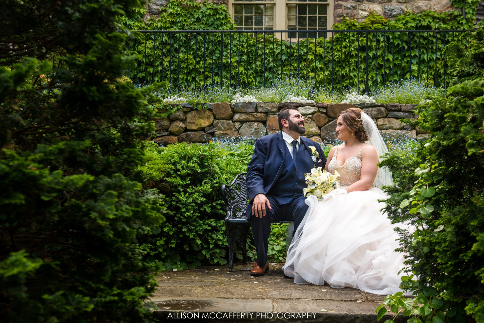 Bride and groom sitting on a bench in a garden