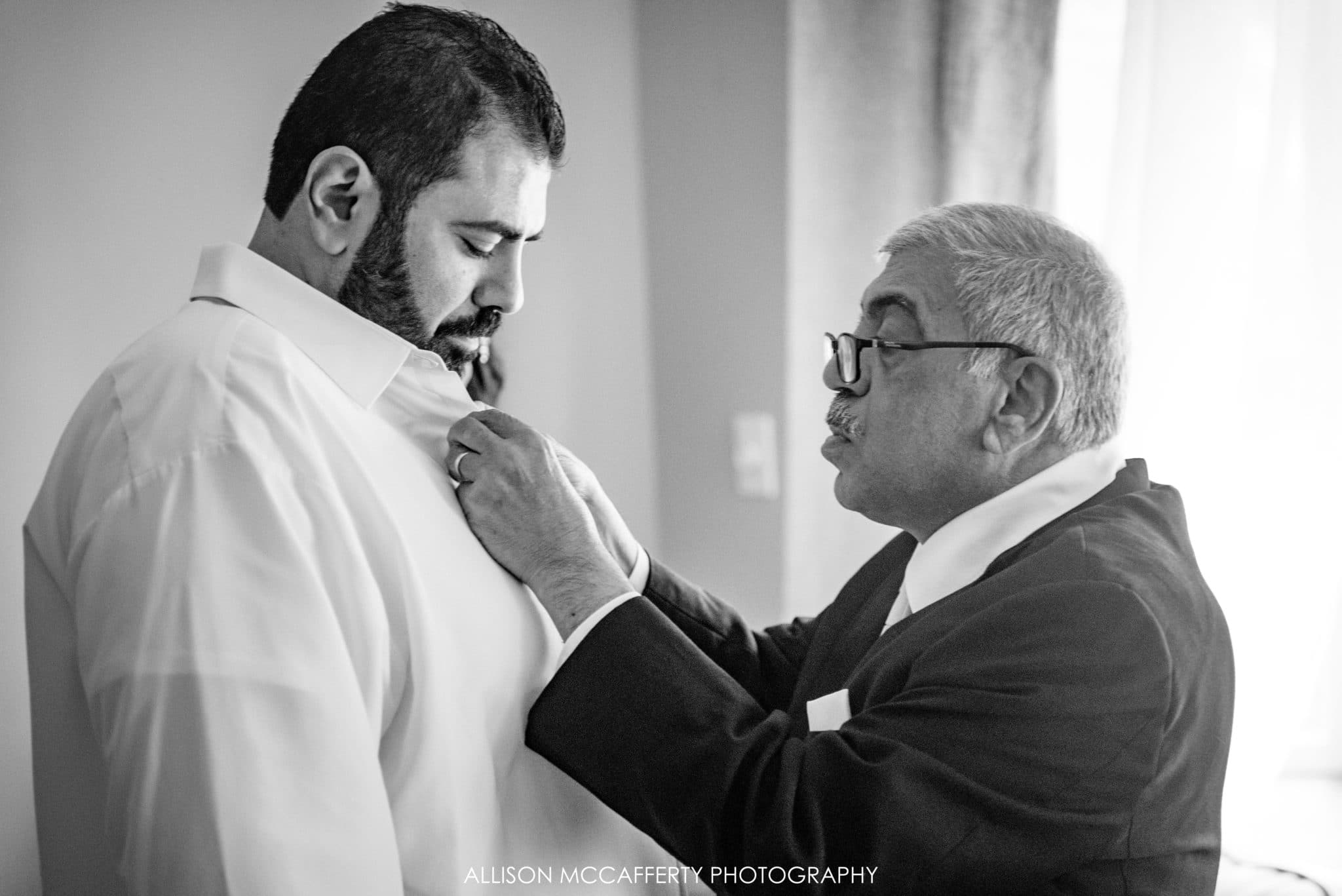 Father of the groom helping to dress his son
