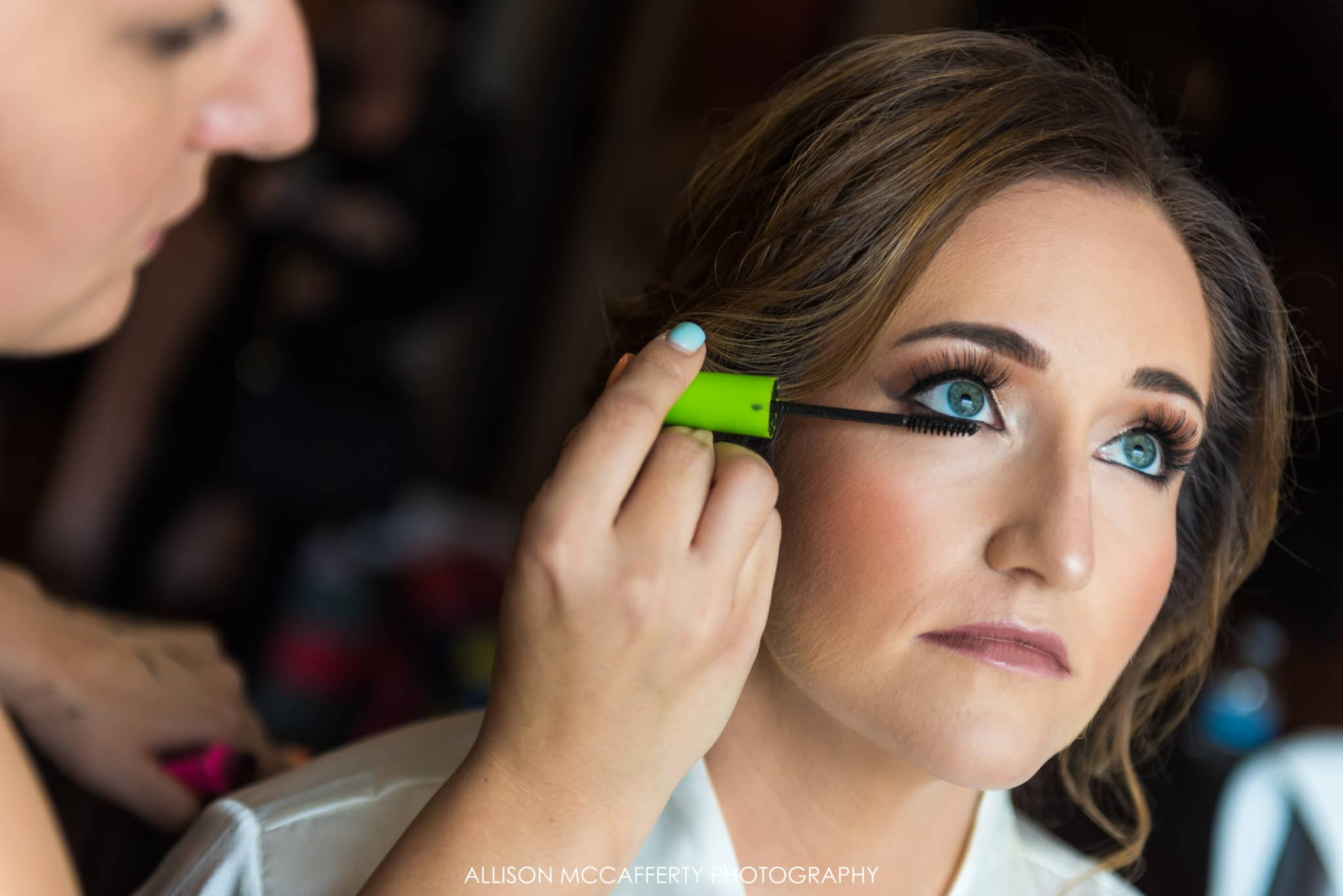 Bride with blue eyes getting makeup done