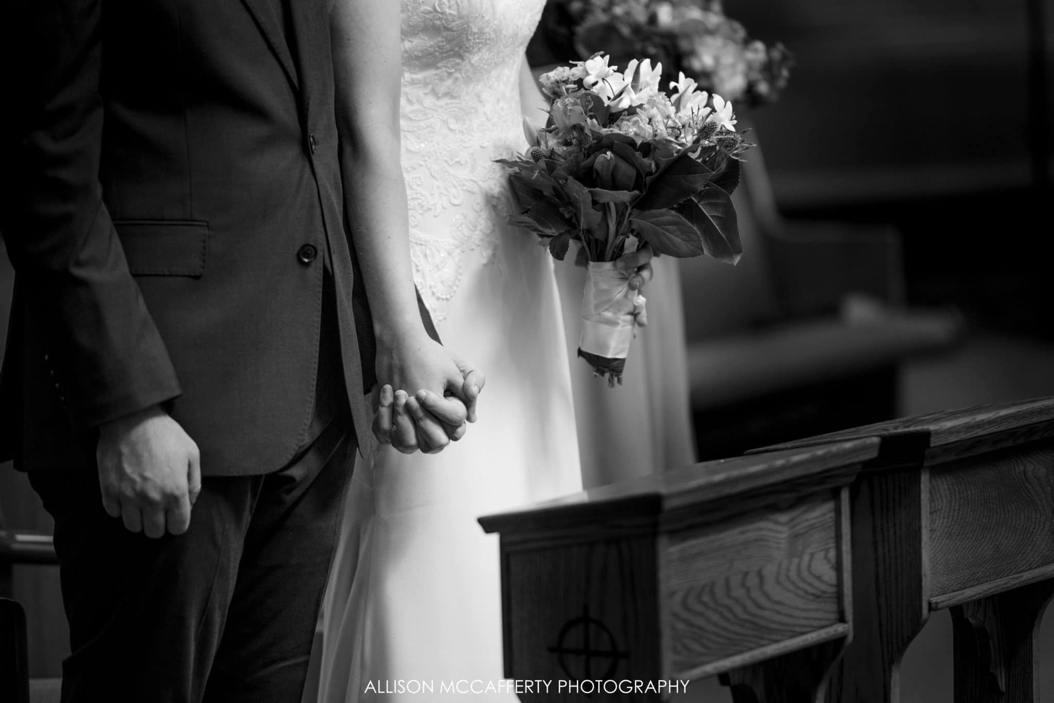 Black and white photo of bride and groom holding hands in church