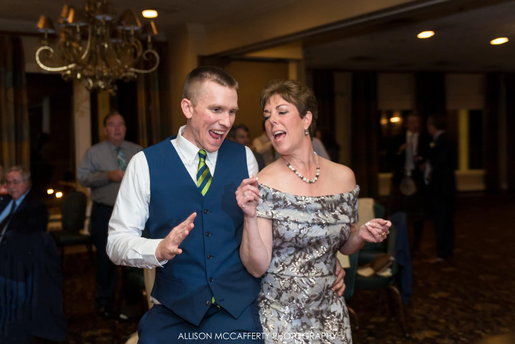 Groom and mother of the bride dancing at wedding reception