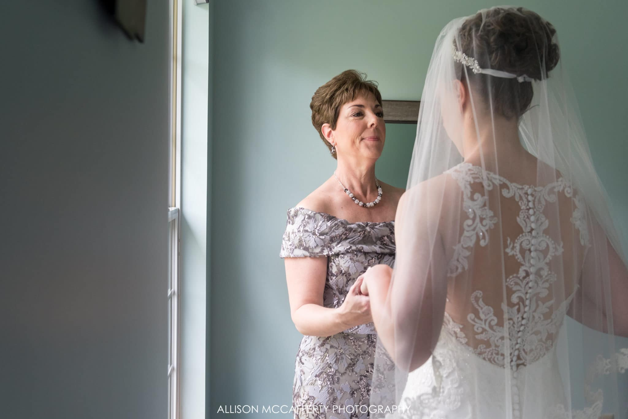 Photo of bride and her mother in front of a window