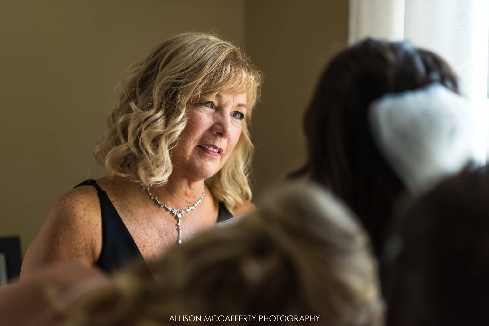 mom looking at her daughter as she gets dressed on her wedding day
