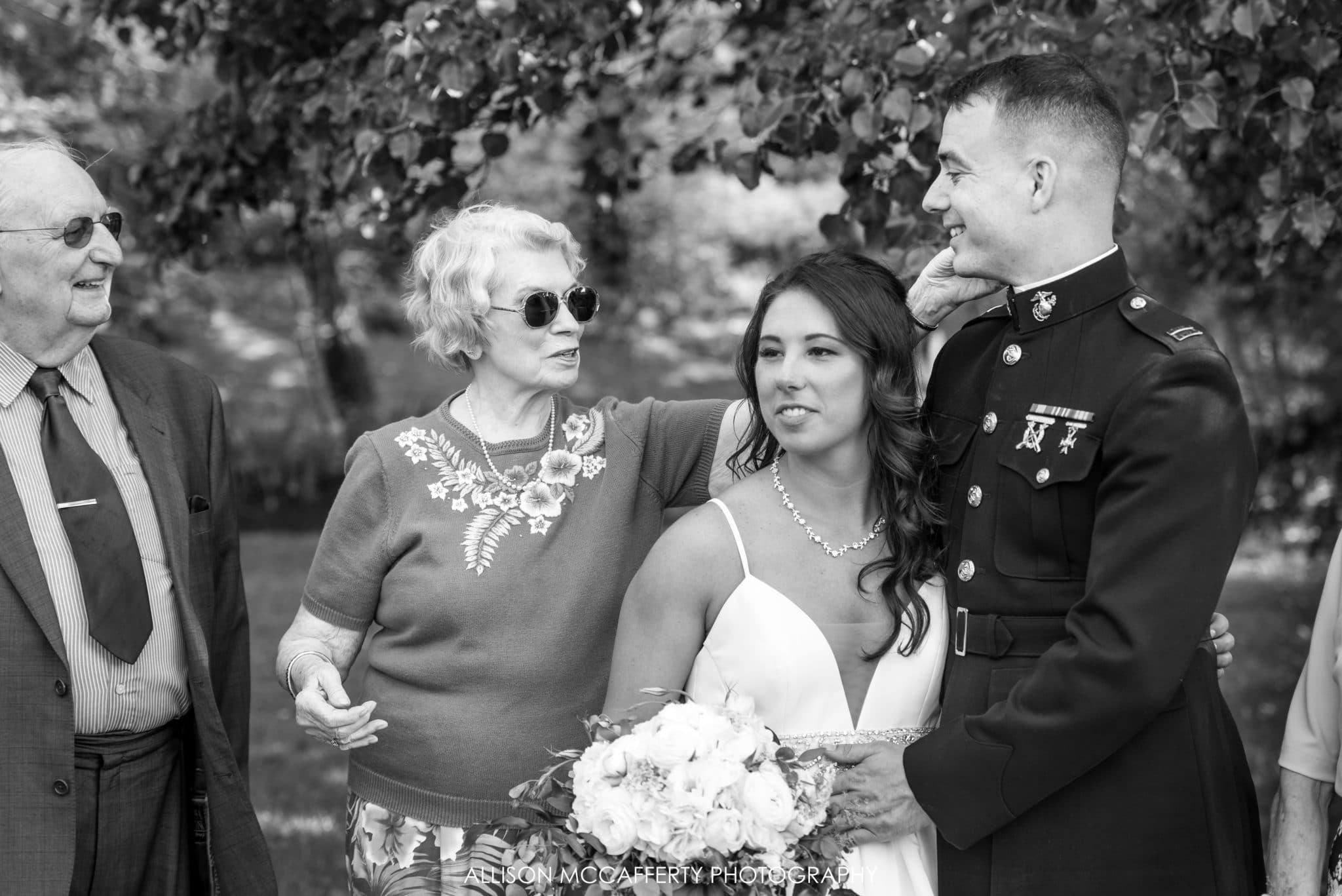 Grandmother touching grandson's face at his wedding