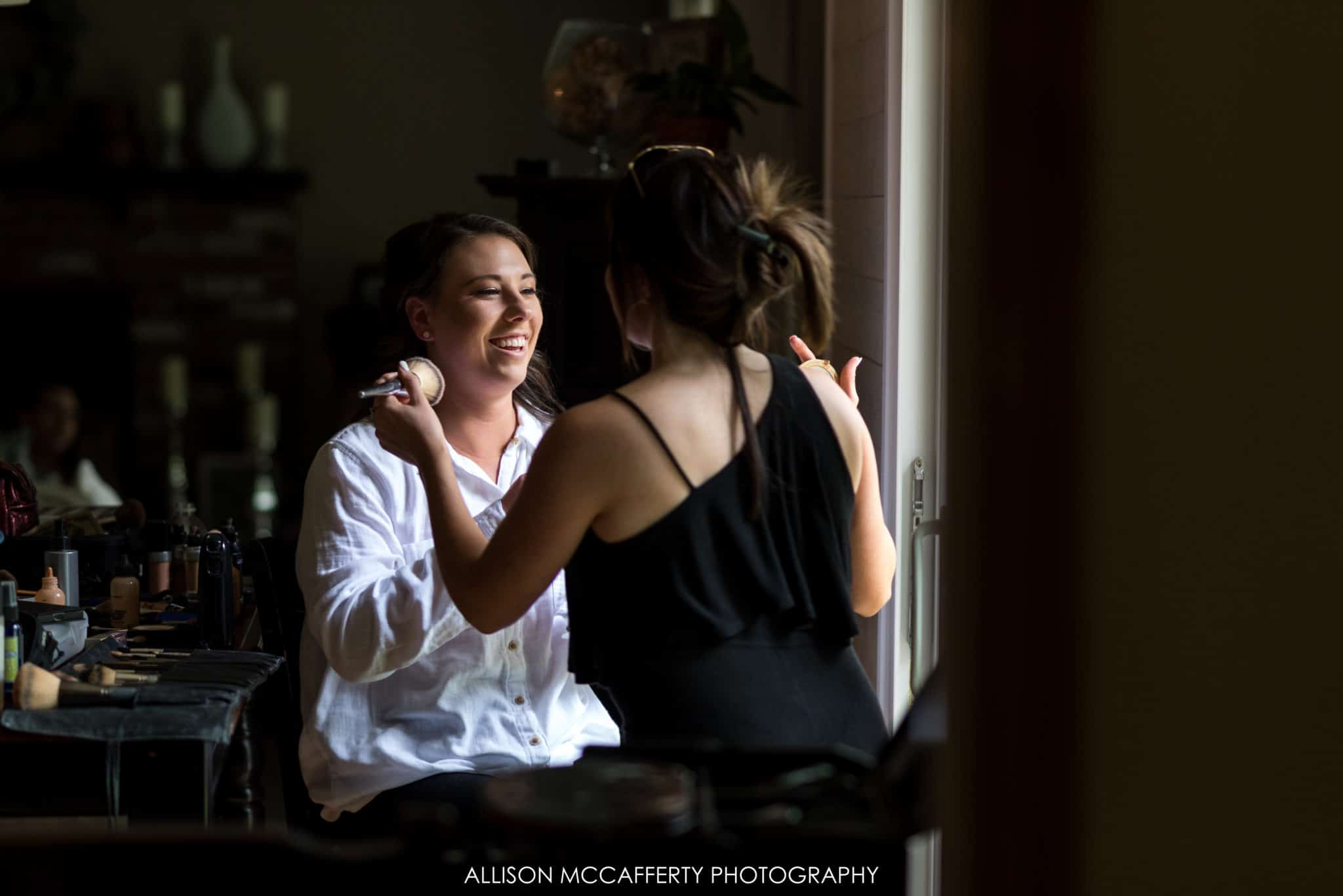 bride sitting in window light getting makeup done