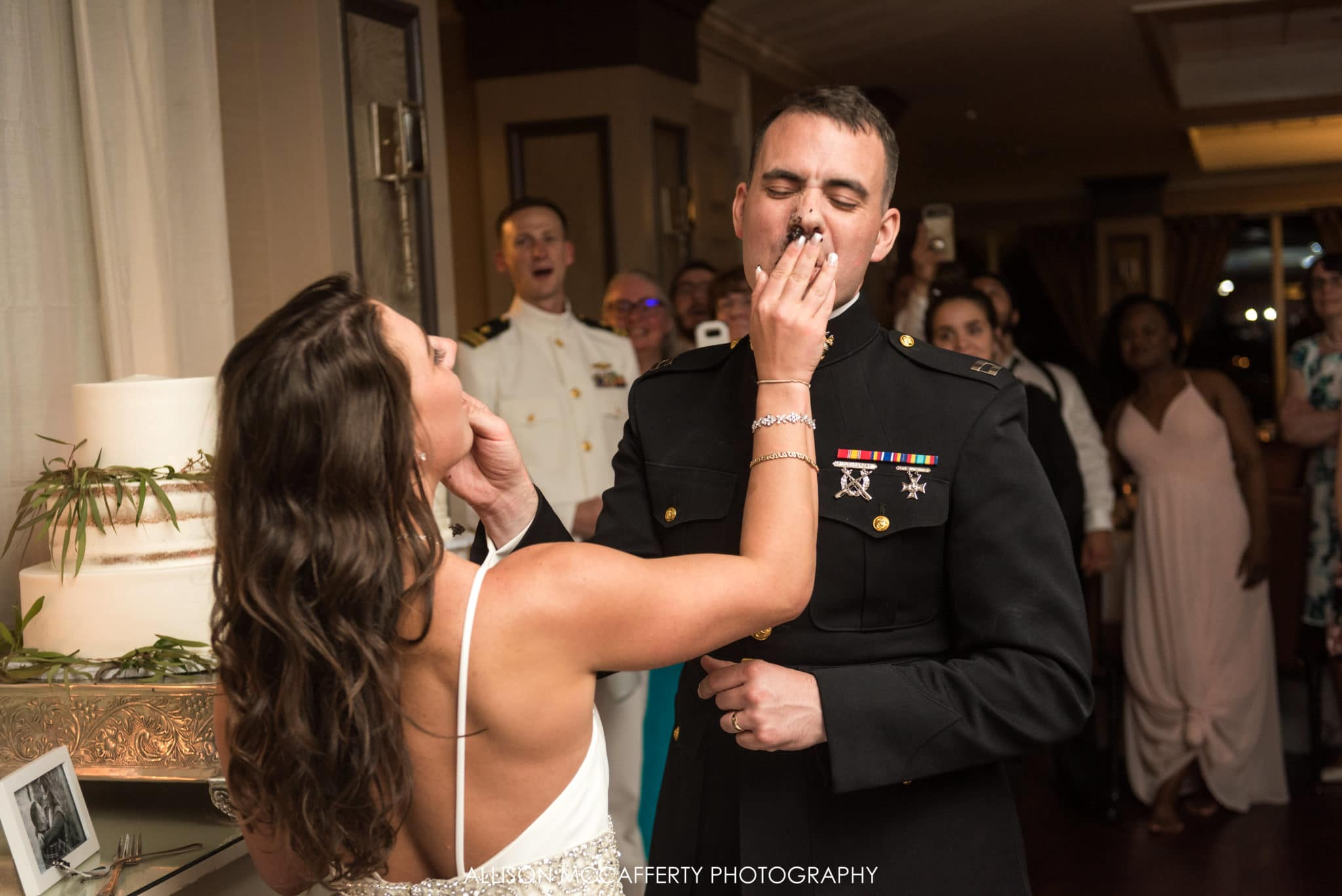 cake smash in grooms face at wedding
