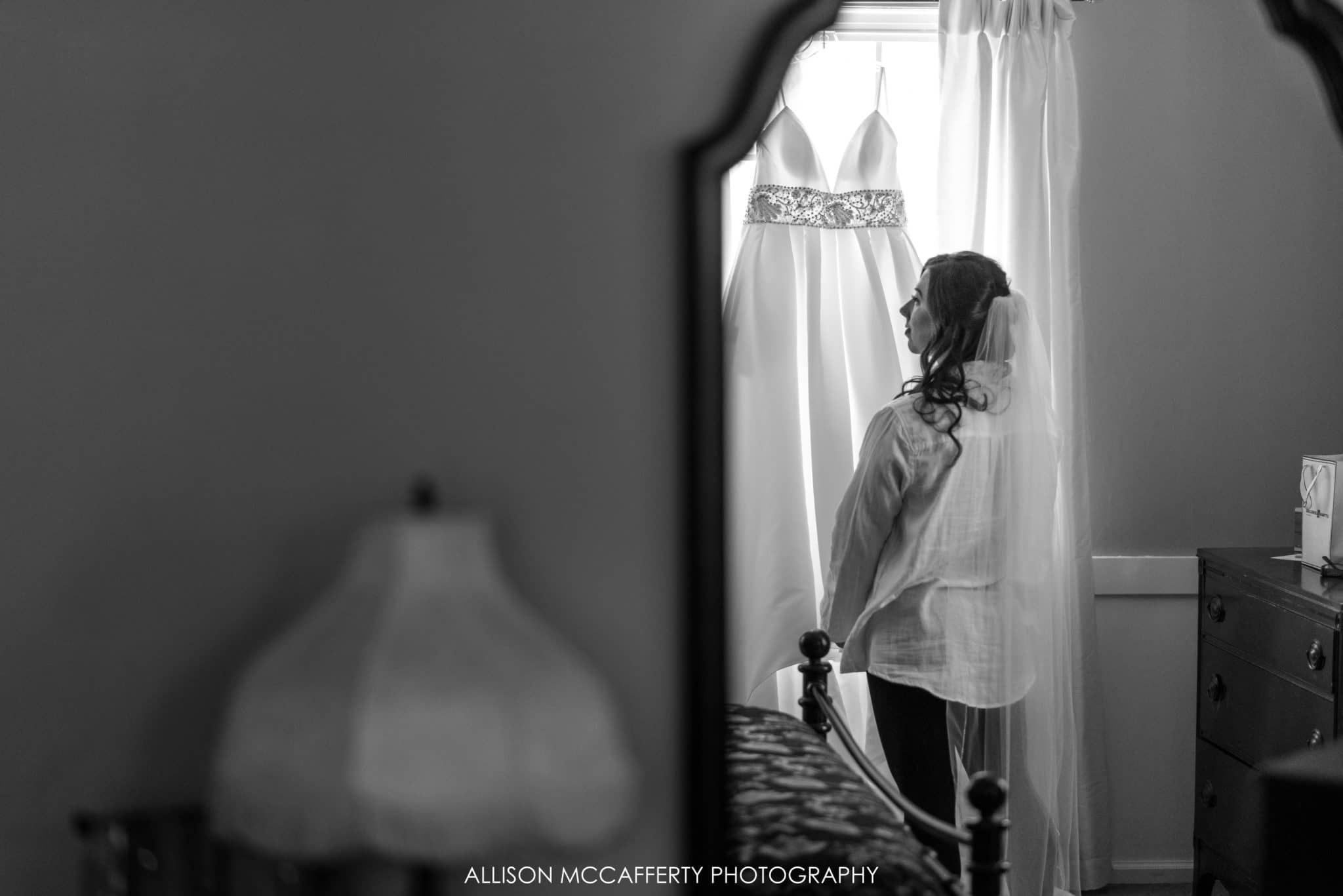 black and white photo of bride looking at her gown in a reflection