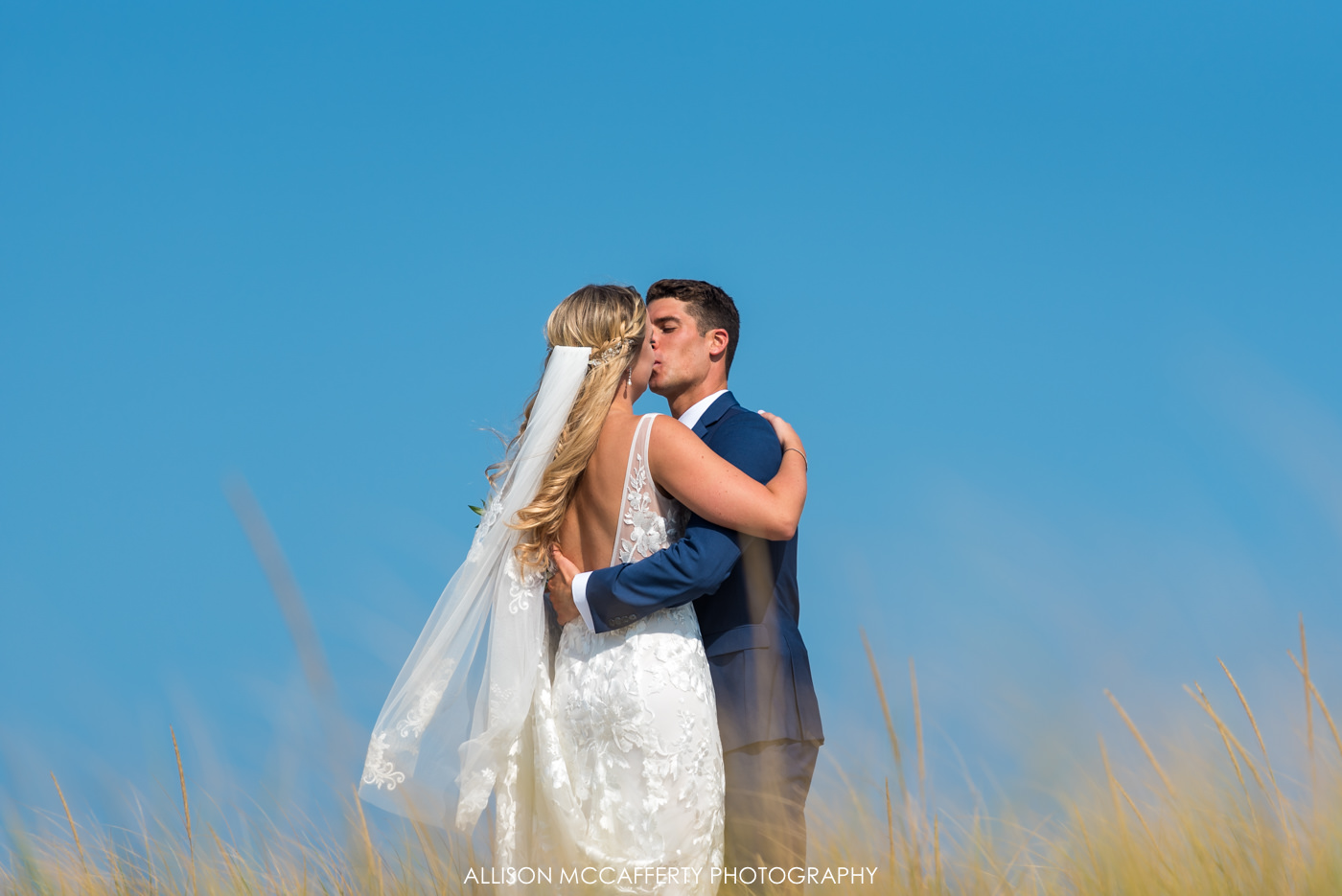 Bride and groom kissing on the dunes of LBI