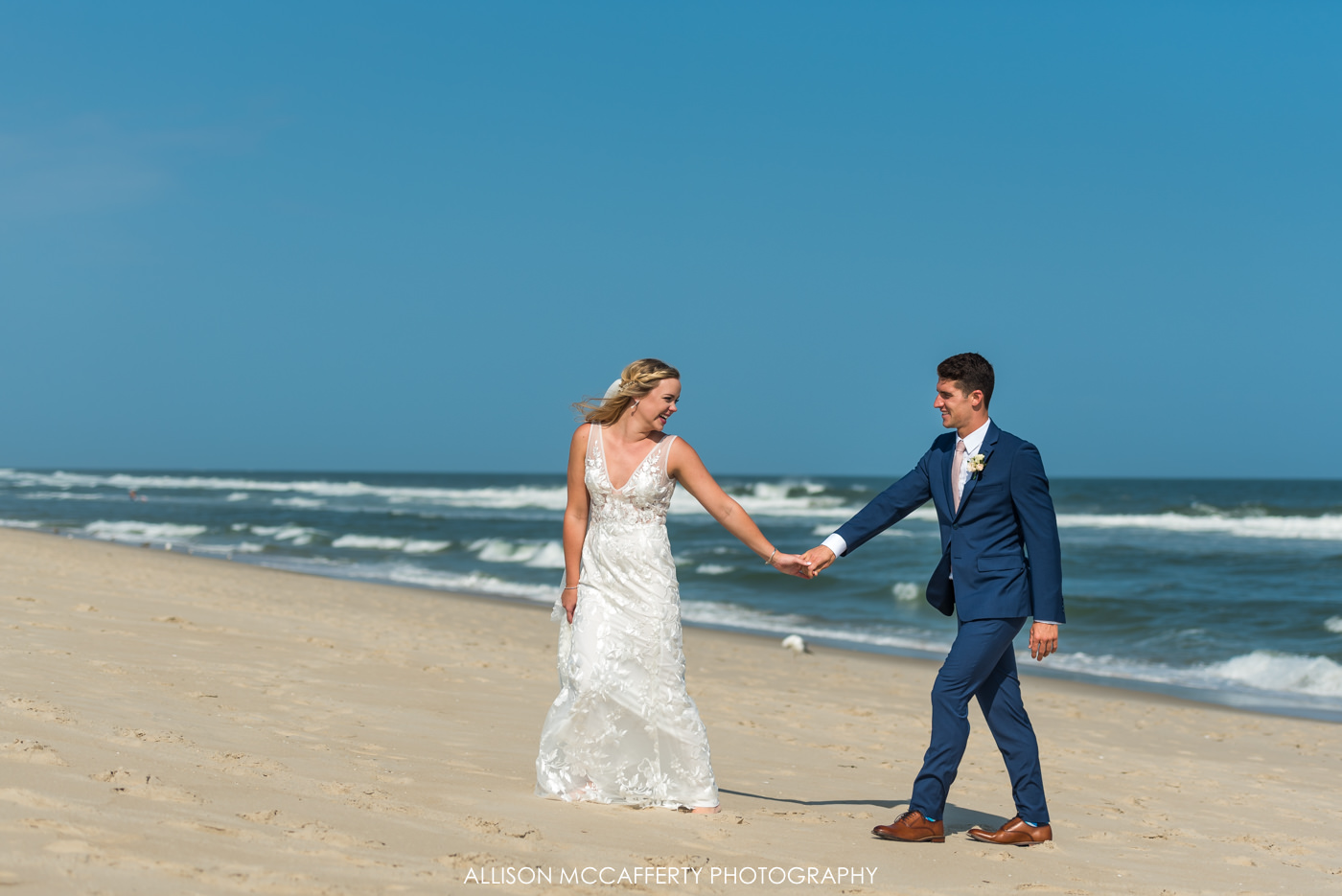 Bride leading groom up the beach in Beach Haven, NJ