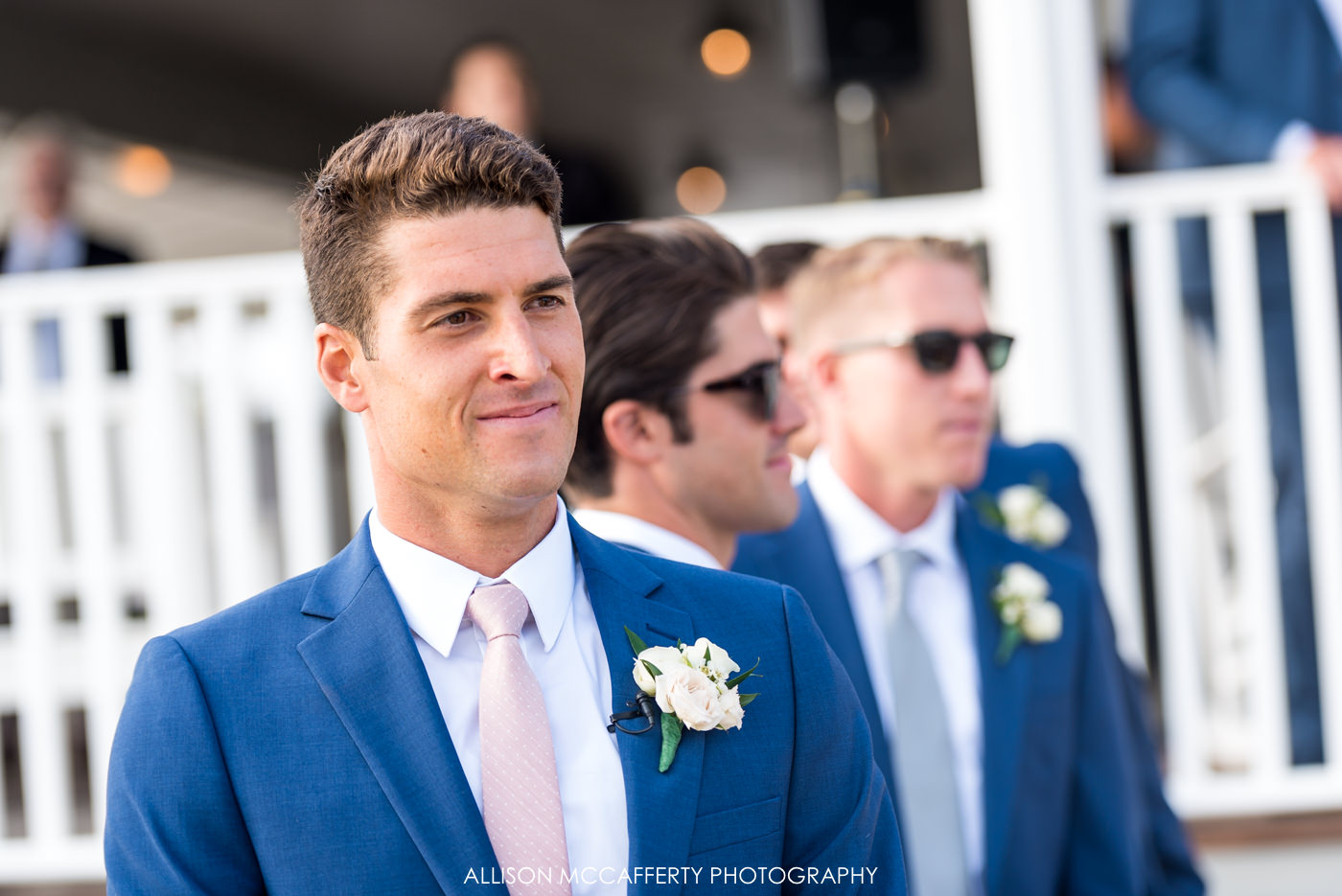 Groom in navy suit and pink tie