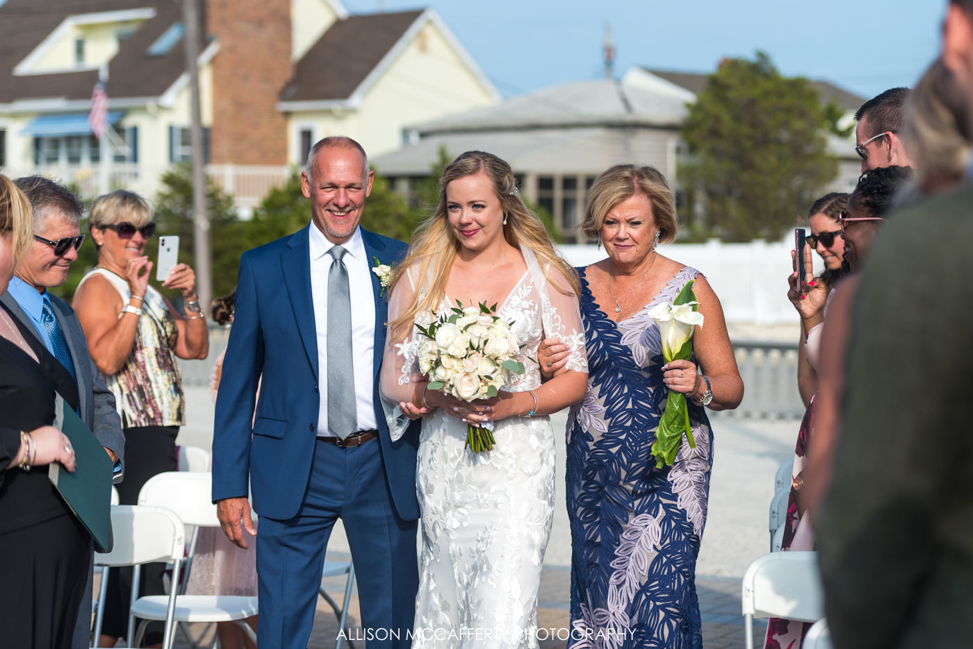Parents walking their daughter down the aisle on her wedding day at Brant Beach Yacht Club