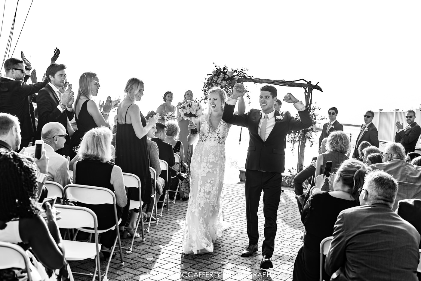 Black and white photo of newly wed couple walking out of their ceremony at Brant Beach Yacht Club
