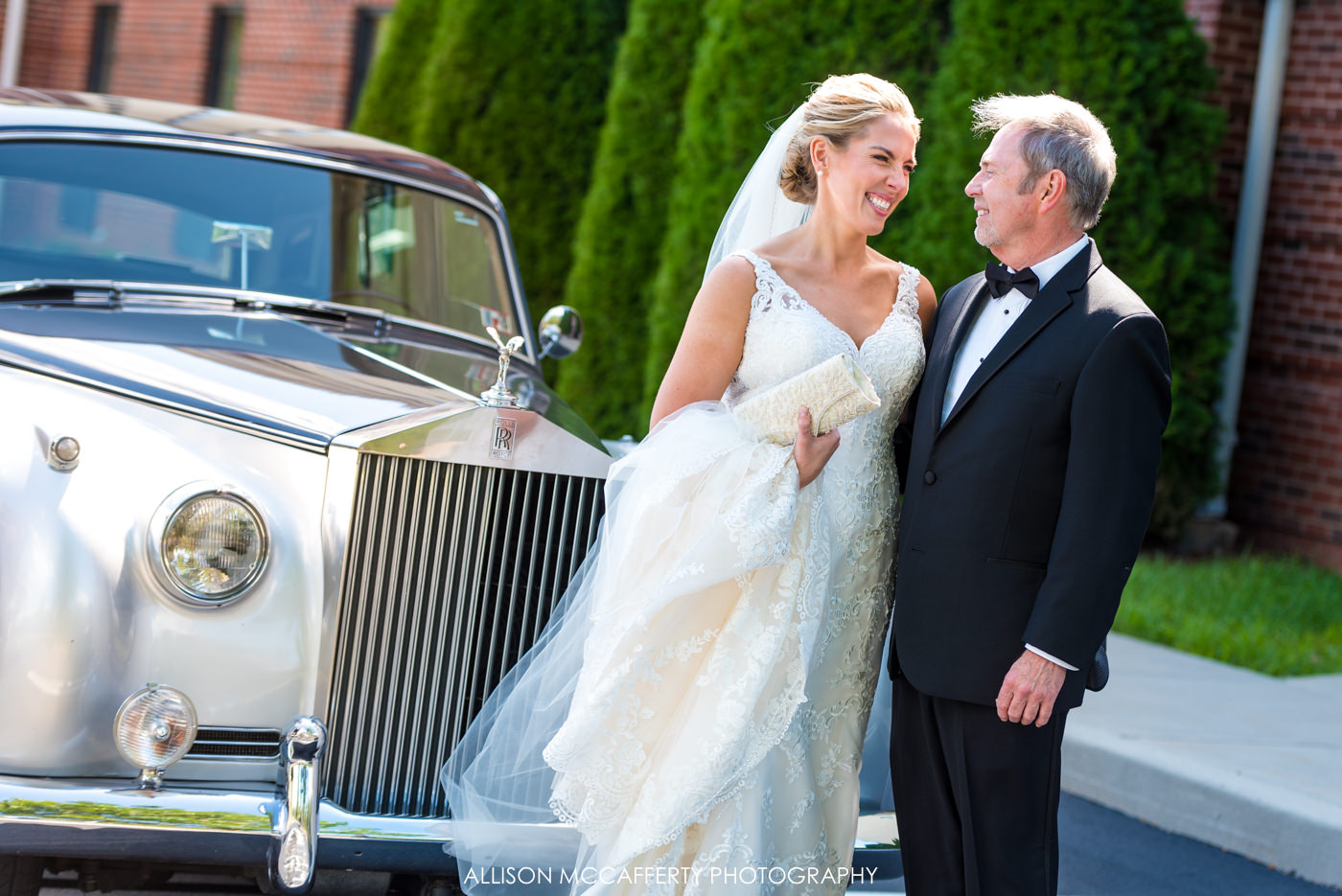 Bride and Father standing in front of a Rolls Royce on wedding day