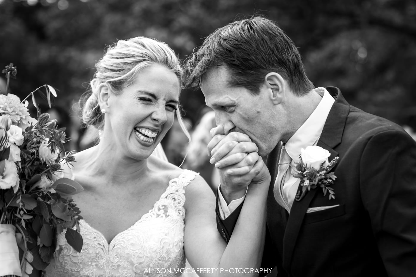 black and white photo of husband kissing his wife's hand